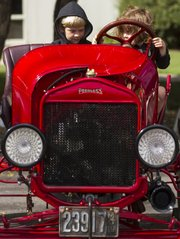 "Five-year-old Quinn Cunningham and her brother Oliver, 7, both of Lawrence, get a chance to sit inside a 1919 Ford ""T"" Speedster during an antique car show held at the Douglas County fairgrounds on Sunday."