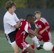 Free State's Josh Hodge, left, fights for a possession in a 1-0 loss to Shawnee Heights on Monday, Oct. 7, 2013, at FSHS.