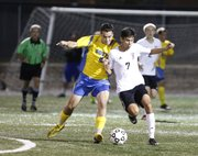 Lawrence High midfielder Narito Mendez competes for the ball against Olathe South midfielder Jake Moore during the first half on Tuesday, Oct. 8, 2013 at Lawrence High School.  Nick Krug/Journal-World Photo