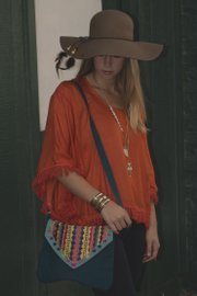 Elizabeth Kennedy wears a bohemian-style outfit from Earthbound Trading Co., 916 Massachusetts St.: orange top, $29.95; skull necklace, $14.95; owl Necklace, $12.95; bangle, $9.95; hat, $24.95; bag, $24.95.