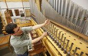 Lawrence resident Tom Watgen, a 25-year voicer for the Reuter Organ Co., adjusts an organ pipe Wednesday. As a voicer, Watgen uses his acute sense for correct musical tones to fine-tune the pipes of the organs.