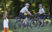 Lawrence police officers Jeff Holtzman, left, and Dan Ashley stop by the East Lawrence Recreation Center while on bike patrol during their shift on Oct. 9, 2013.