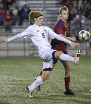 Free State's Alex Trent (8) kicks the ball away from Olathe North's Jack Chalfant (6) during their soccer match Thursday at FSHS.