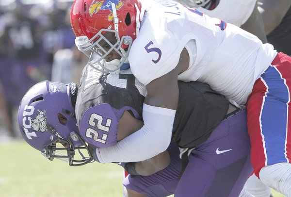 Kansas safety Isiah Johnson (5) gets all over TCU's Aaron Green (22) during a tackle in the second half on Saturday, Oct. 12, 2013.