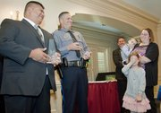 From left Lawrence Police Officer Sutagee Anglin and Sgt. Ted Bordman, laugh as Addalyne Egidy, 7, covers her face. Addalyne, her mother, Erin Egidy, and brother Aiden Egidy, 3, were introduced while receiving a Silver Valor Award on behalf of their husband and father, Officer Robert Egidy, who is deployed to Afghanistan with the U.S. Army Reserve. The three law enforcement officers, who rescued an unconscious man from a burning house in December 2012, were among 40 first responders honored Tuesday at the Leadership Lawrence Valor Public Safety Awards.