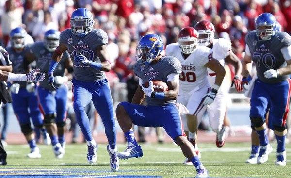 Kansas running back Darrian Miller makes a cut against Oklahoma during the first quarter on Saturday, Oct. 19, 2013 at Memorial Stadium.