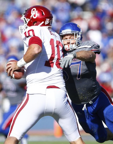 Kansas linebacker Jake Love wraps up Oklahoma quarterback Blake Bell out of the pocket during the second quarter on Saturday, Oct. 19, 2013 at Memorial Stadium.