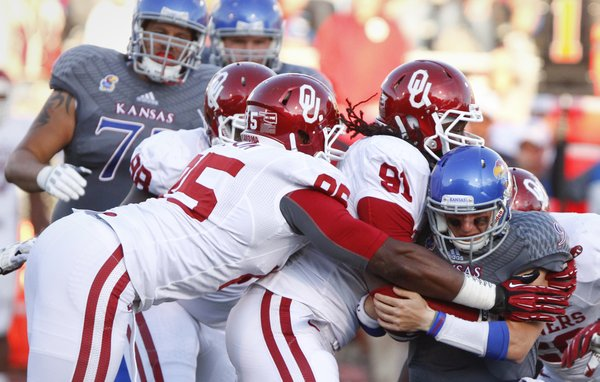 Kansas quarterback Jake Heaps is sacked by Oklahoma defenders Charles Tapper (91) and Geneo Grissom on the Jayhawks' last drive of the game, Saturday, Oct. 19, 2013 at Memorial Stadium.