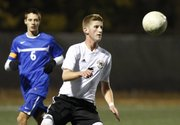 Free State senior midfielder Chris Allen controls the ball in front of Leavenworth defender Evan Lott during the first half on Tuesday, Oct. 22, 2013 at Free State High School.