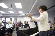 """Class instructor Kelley Hunt stands up to applaud her students during a performance by a group of seniors enrolled in the """"Joyful Singing"""" course, Tuesday, Oct. 22, 2013 at the Osher Institute, 1515 St. Andrews Drive."""