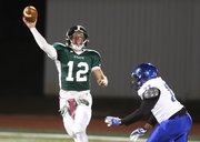 Free State quarterback Joe Dineen throws as he is pressured by Leavenworth defensive lineman Sean Young during the first half on Friday, Oct. 25, 2013 at Free State High School.