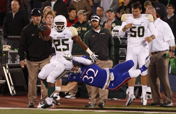Kansas linebacker Schyler Miles is slung out of bounds while trying to bring down Baylor running back Lache Seastrunk during the first quarter on Saturday, Oct. 26, 2013.