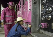 Judi Long, of Lawrence, signs a pink firetruck in honor of her friend, Sonja Hutchinson, as Sedgwick County firefighter and Guardians of the Ribbon volunteer James Tiffany watches, Saturday night outside of the Crown Toyota Pavillion in South Lawrence. The firetruck was on display as part of the Stepping Out Against Breast Cancer event.