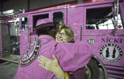 Jane Kay, of Lawrence, a three-year cancer survivor, receives a hug from a Guardians of the Ribbon volunteer before signing a pink firetruck on display Saturday night outside of the Crown Toyota Pavillion in South Lawrence. The firetruck was on display as part of the Stepping Out Against Breast Cancer event.