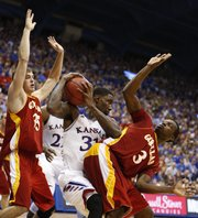 Kansas center Jamari Traylor pulls a rebound away from Pittsburg State defenders Cody Gafford (35) and Jerrod Gaston (3) during the second half of an exhibition game on Tuesday, Oct. 29, 2013 at Allen Fieldhouse.