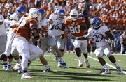 Kansas running back James Sims looks for a hole as the Texas defense closes in during the second quarter on Saturday, Nov. 2, 2013 at Darrell K. Royal Stadium in Austin, Texas.