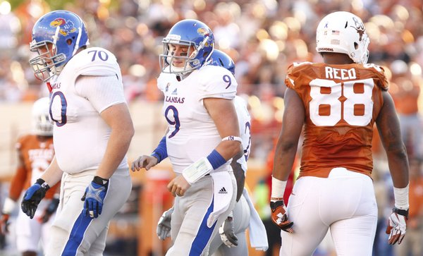 Kansas quarterback Jake Heaps bemoans a missed opportunity in the fourth quarter as he heads off the field with offensive lineman Gavin Howard after being sacked by the Texas defense during the fourth quarter on Saturday, Nov. 2, 2013 at Darrell K. Royal Stadium in Austin, Texas.