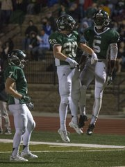 Free State's Khadre Lane (5) and Keith Loneker (20) celebrate Lane's third-quarter touchdown reception as teammate Blake Winslow (7) watches during their football game against Shawnee Mission Northwest Friday, Nov. 8, 2013, at Free State.