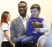 Kansas guard Naadir Tharpe holds Jayhawk fan Brock Bailey, 4, before tipoff of the Jayhawks' regular-season opener against Louisiana Monroe, Friday, November, 8, 2013 at Allen Fieldhouse. Tharpe was suspended for the first game because of an NCAA violation.