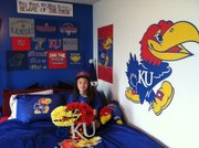 Brenna of Omaha, Neb., in her KU-themed bedroom — with homemade pinata.
