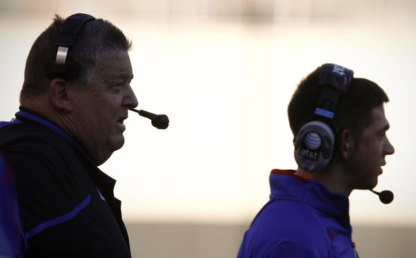 Kansas head coach Charlie Weis and his son, Charlie Weis Jr. watch from the sidelines during the second quarter on Saturday, Nov. 9, 2013 at Boone Pickens Stadium in Stillwater, Oklahoma.