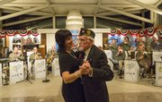 World War II veteran Chuck Benedict dances with Mary Williams, both of Lawrence, in front of a USO-style band Sunday evening at the Dole Institute of Politics during a celebration for veterans.