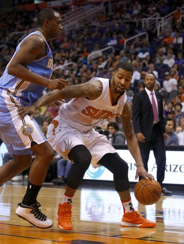 Phoenix Suns power forward Marcus Morris (15), right, drives on Denver Nuggets power forward Darrell Arthur (00) in the third quarter during an NBA basketball game on Friday, Nov. 8, 2013, in Phoenix. The Suns defeated the Nuggets 114-93. (AP Photo/Rick Scuteri)