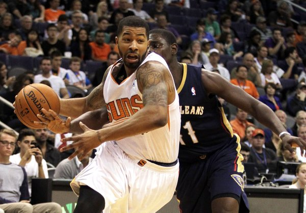 Phoenix Suns forward Markieff Morris, left, drives past New Orleans Pelicans guard Jrue Holiday, right, in the third quarter during an NBA basketball game on Sunday, Nov. 10, 2013, in Phoenix. The Suns defeated the Pelicans 101-94. (AP Photo/Rick Scuteri)