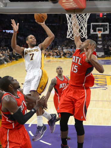 Los Angeles Lakers guard Xavier Henry, upper left, puts up a shot as Atlanta Hawks forward Paul Millsap, left, and Atlanta Hawks center Al Horford, of the Dominican Republic, defend during the second half of their NBA basketball game, Sunday, Nov. 3, 2013, in Los Angeles. The Lakers won 105-103. (AP Photo/Mark J. Terrill)