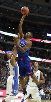 Kansas forward Andrew Wiggins floats for a shot over Duke guard Tyler Thornton during the second half of the Champions Classic matchup on Tuesday, Nov. 12, 2013 at the United Center in Chicago.