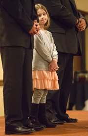 Seven-year-old Addalyne Egidy, of Lawrence, stands in, in place of her father Officer Robert Egidy, to receive his Distinguished Service Award, Thursday night at the Holidome.