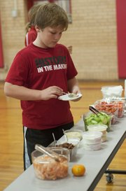 Liam Elliott, 11, fills a plate with healthy snacks such as pita bread, cucumbers, carrots and almonds — just to name a few nutritious eats — at Liberty Memorial Central Middle School last week at an after-school fitness and nutrition program, Smart Strength. The Merc supplied nutritious food and taught kids the value of eating right.