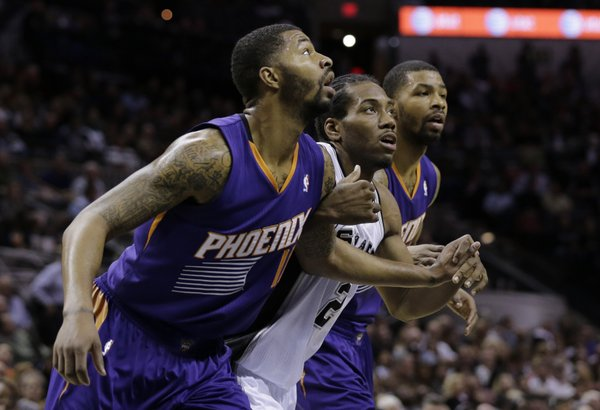 San Antonio Spurs' Kawhi Leonard, center, is boxed in by Phoenix Suns' Markieff Morris, left, and Marcus Morris, right, during the first half of an NBA basketball game, Wednesday, Nov. 6, 2013, in San Antonio. (AP Photo/Eric Gay)