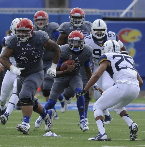 Kansas quarterback Montell Cozart looks to make a move against West Virginia safety Darwin Cook during the first quarter on Saturday, Nov. 16, 2013 at Memorial Stadium.