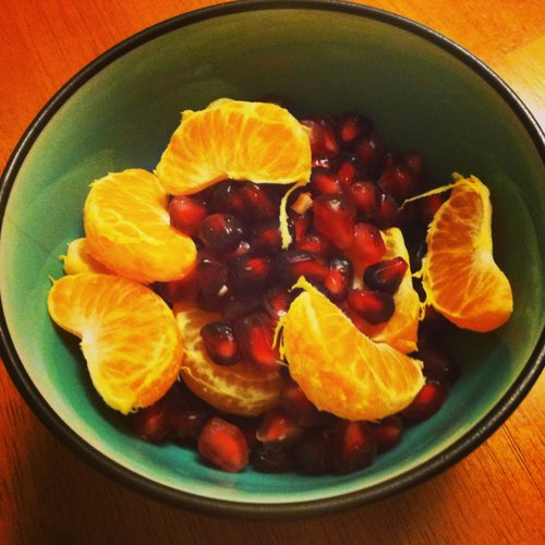 About half a pomegranate with tangerine slices.