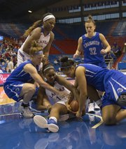Kansas' Chelsea Gardner, center, wrestles with Creighton's Sarah Nelson, left, and Alexis Akin-Otiko, right, for control of a loose ball during their game Sunday at Allen Fieldhouse.