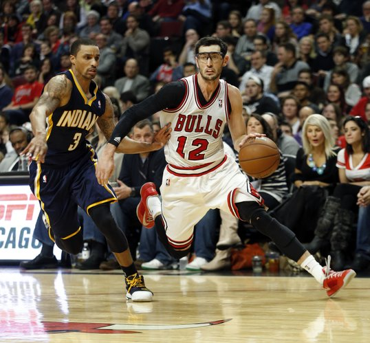 Chicago Bulls guard Kirk Hinrich (12) drives to the basket against Indiana Pacers guard George Hill (3) during the second half of an NBA basketball game in Chicago, Saturday, Nov. 16, 2013. The Bulls won 110-94. (AP Photo/Kamil Krzaczynski)