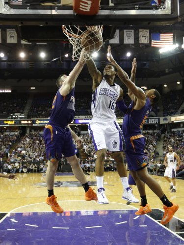 Sacramento Kings guard Ben McLemore, left, stuffs against Phoenix Suns' Miles Plumlee, center and Channing Frye during the third quarter of an NBA basketball game in Sacramento, Calif., Tuesday, Nov. 19, 2013. The Kings won 107-104.(AP Photo/Rich Pedroncelli)