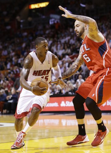 Miami Heat guard Mario Chalmers (15) drives past Atlanta Hawks center Pero Antic (6) of Macedonia, during the first half of an NBA basketball game, Tuesday, Nov. 19, 2013 in Miami. The Heat defeated the Hawks 104-88. (AP Photo/Wilfredo Lee)