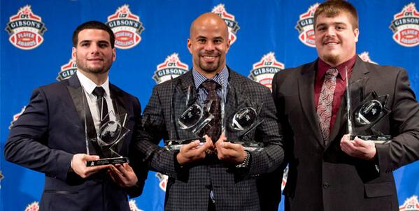 Former Jayhawk Jon Cornish (center) poses with two of his Calgary Stampeder teammates Thursday night after hauling in the CFL's Most Outstanding Player and Most Outstanding Canadian awards following another stellar season in which he recorded the fourth highest single-season rushing total in CFL history. (Photo courtesy of the @CFL Twitter account)