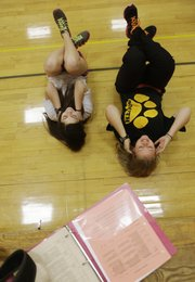 With their workout notebook on the bleachers above them, Lilian Khan, left, and Carli Stellwagon, do sit-ups during their individual workouts. The two are in teacher Amy Hoffsommer's PE class, during which they use heart monitors purchased by the Lawrence Schools Foundation through a Teacher Innovation Grant.