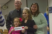 Mikalah Clark, 8, and her sister Alexis Clark, 11, hold a sign for a family picture with parents Shannon and Tonya Clark of Lawrence just before their adoption finalization hearing on Friday. Seven of the girls' nine siblings were on hand in Douglas County District Court for the milestone, scheduled during National Adoption Week.