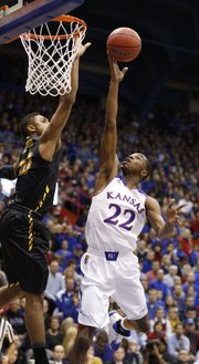 Kansas guard Andrew Wiggins lays up a bucket over Towson forward Jerrelle Benimon during the first half on Friday, Nov. 22, 2013 at Allen Fieldhouse.