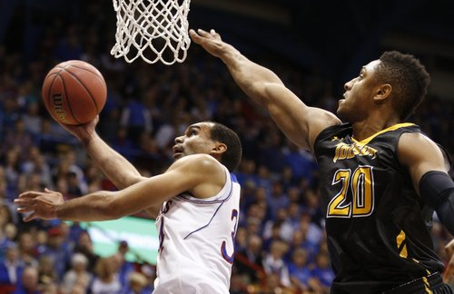 Kansas forward Perry Ellis hooks a shot around Towson forward Jerrelle Benimon during the first half on Friday, Nov. 22, 2013 at Allen Fieldhouse.