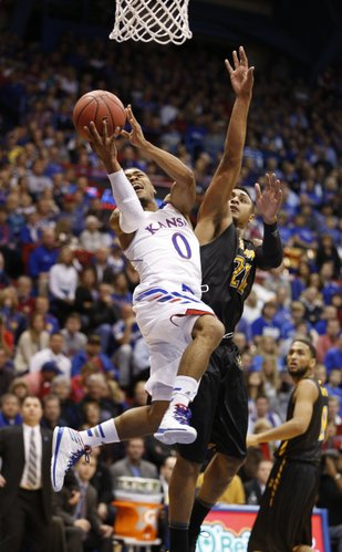 Kansas guard Frank Mason hangs for a shot as he is fouled by Towson forward Jerrelle Benimon during the first half on Friday, Nov. 22, 2013 at Allen Fieldhouse.