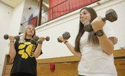 Carli Stellwagon, left, and Lilian Khan, both 9th-graders at Lawrence High School, lift weights during their individual workouts The two are in teacher Amy Hoffsommer's PE class, during which they use heart monitors purchased by the Lawrence Schools Foundation.