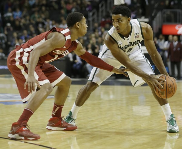Oklahoma's Isaiah Cousins (11) guards Michigan State's Gary Harris (14) during the first half of the championship game in the Coaches vs. Cancer NCAA college basketball game on Saturday, Nov. 23, 2013, in New York. (AP Photo/Frank Franklin II)