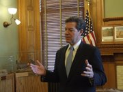 Gov. Sam Brownback speaks with reporters after meeting Monday with school officials and legislative leaders about ways to avoid future litigation over school finance.