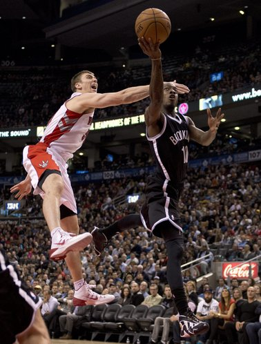 Brooklyn Nets guard Tyshawn Taylor (10) drives to the hoop past Toronto Raptors forward Tyler Hansbrough (left) during the second half of an NBA basketball game in Toronto on Tuesday, Nov. 26, 2013. (AP Photo/The Canadian Press, Frank Gunn)