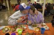 Ronnie Copp kisses his wife of 34 years, Patricia, before they took part in the annual LINK Thanksgiving meal at First Christian Church, 1000 Kentucky St., on Thursday. People from all over the community filled the small basement for a free Thanksgiving dinner.